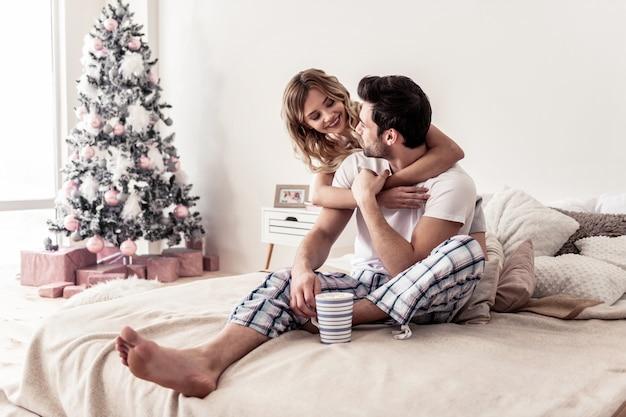 Verliefd. mooie blonde vrouw, gekleed in korte broek knuffelen een bebaarde knappe man terwijl ze een ochtend samen doorbrengen