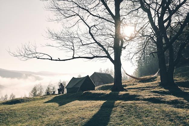 Verliefd op de natuur. jonge man zit in de buurt van de tent tijdens het kamperen in de bergen