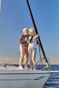 Verliefd op de volledige lengte van een gelukkig senior paar dat handen vasthoudt en elkaar aankijkt terwijl ze staan