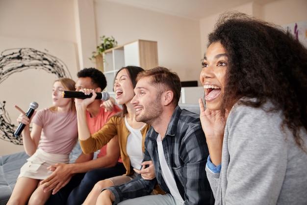 Verliefd op karaoke-groep jonge vrienden die plezier hebben met zingen met microfoon tijdens het spelen