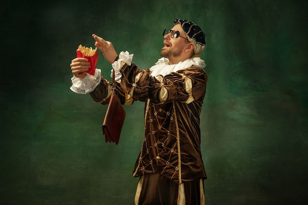 Verliefd op smaak. portret van middeleeuwse jonge man in vintage kleding met houten frame op donkere achtergrond. mannelijk model als hertog, prins, koninklijk persoon. concept vergelijking van moderne tijdperken, mode.