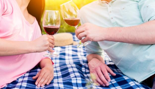 Verliefd paar die op blauwe geruite plaid liggen en wijnglazen roosteren