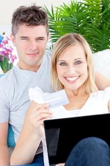 Verliefd paar die op de bank met laptop en een kaart liggen
