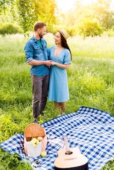 Verliefd paar knuffelen staande door geruite plaid op picknick