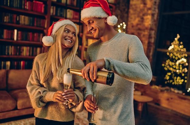 Verliefd romantisch paar dat geluk voelt over hun romance die kerst of nieuwjaar samen doorbrengt. een man schenkt champagne in glazen.