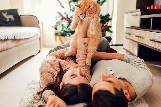 Verliefd stel dat bij de kerstboom ligt en thuis met een kat speelt
