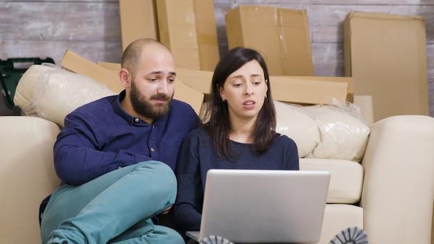 Verliefd stel is net verhuisd naar hun nieuwe appartement en doet online winkelen op laptop. kartonnen dozen op de achtergrond.
