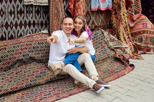Verliefd stel koopt een tapijt en handgemaakt textiel op een oosterse markt in turkije. knuffels en vrolijke blije gezichten van mannen en vrouwen