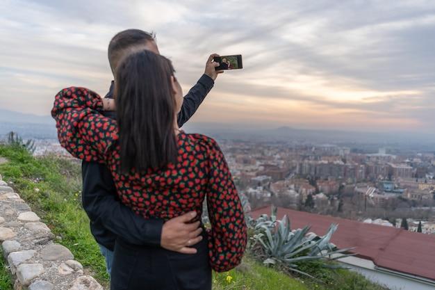 Verliefd stel maakt een selfie bij zonsondergang met smartphone