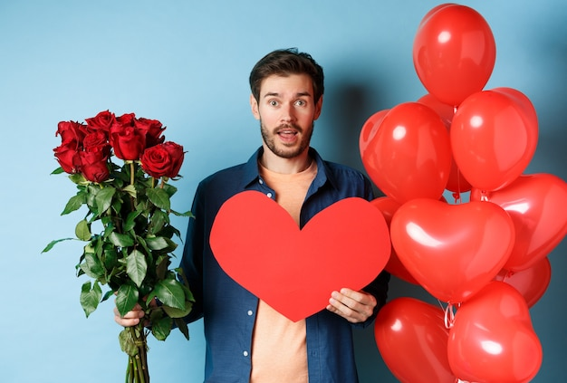 Verliefde man brengt verrassingsgeschenken op een romantische date, houdt een boeket rode rozen en valentijn rood hart vast, staat in de buurt van ballonnen en kijkt naar minnaar, blauwe achtergrond.