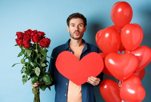 Verliefde man wenst gelukkige valentijnsdag, wachtend op een kus op een romantische date, met rode rozen, rood hart en ballonnen, staande over blauwe achtergrond.