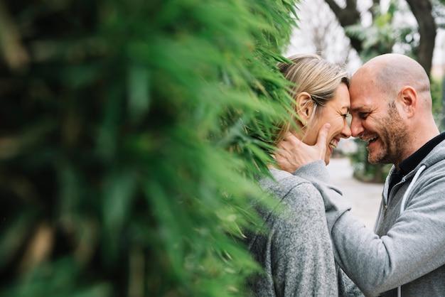 Verliefde paar achter boom