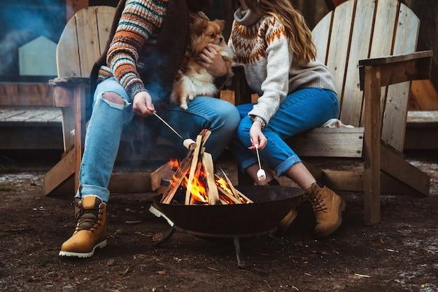 Verliefde paar bereidt marshmallows bij het vuur.