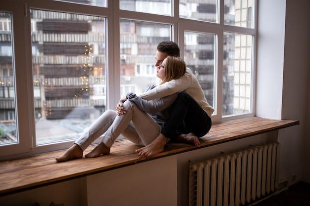 Verliefde paar bij elkaar zitten en kijken naar venster. valentijnsdag.