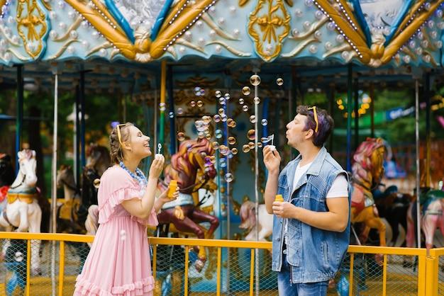 Verliefde paar blaast zeepbellen naar elkaar, ze zijn gelukkig en lachen in een pretpark