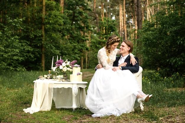 Verliefde paar bruid en bruidegom zitten op een stoel in het bos en lachen. bruiloftsdecoraties en accessoires liggen op tafel