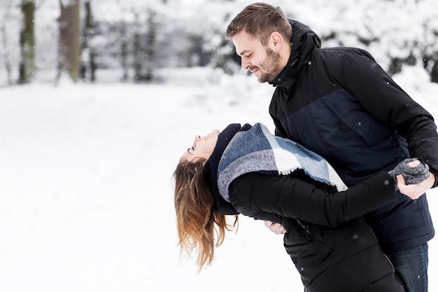 Verliefde paar dansen in het besneeuwde park