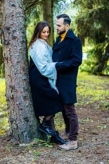 Verliefde paar gekleed in jassen in het bos