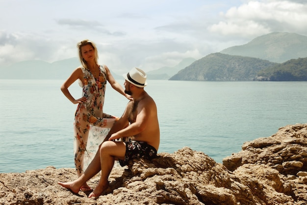 Verliefde paar genieten van huwelijksreis op rots met luxe uitzicht wandelen met emotie op azuurblauwe zee achtergrond. gelukkige geliefden op romantische reis hebben plezier op zomervakantie. concept romantiek en ontspanning
