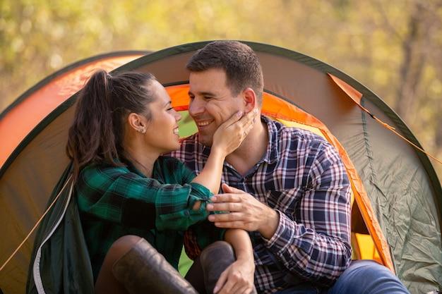 Verliefde paar glimlachen terwijl ze naar elkaar kijken voor de tent. romantische sfeer
