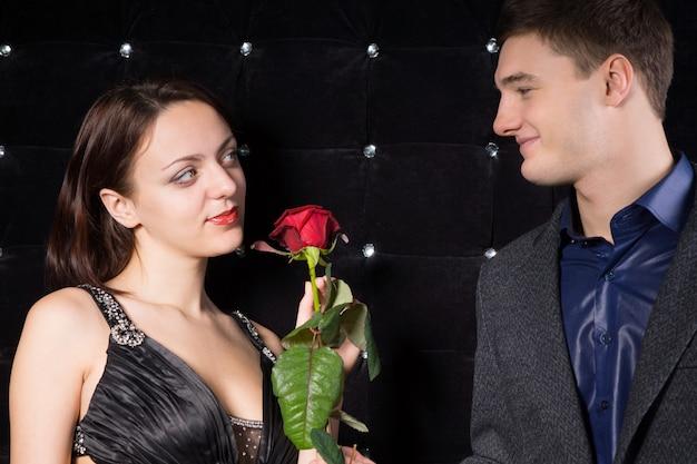 Verliefde paar glimlachend naar elkaar met tedere uitdrukkingen over een enkele rode roos die valentijnsdag symboliseert, een voorstel voor haar hand in huwelijk of jubileum