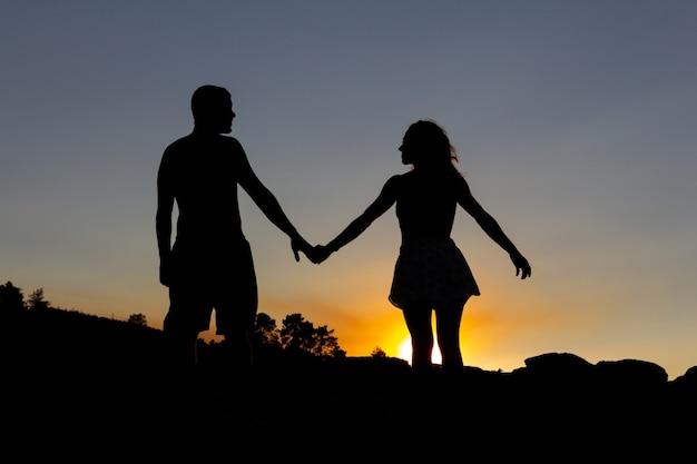 Verliefde paar hand in hand in een romantische zonsondergang op een meer. achtergrondverlichting. ruimte kopiëren. herfst.