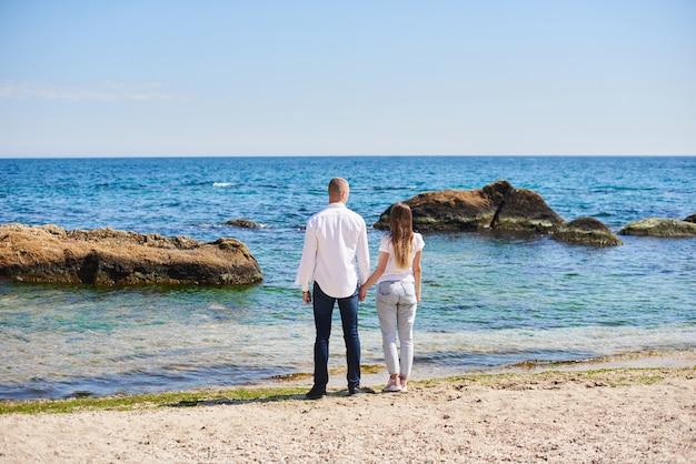 Verliefde paar hand in hand op een tropisch strand met een turquoise water en rotsen op de achtergrond