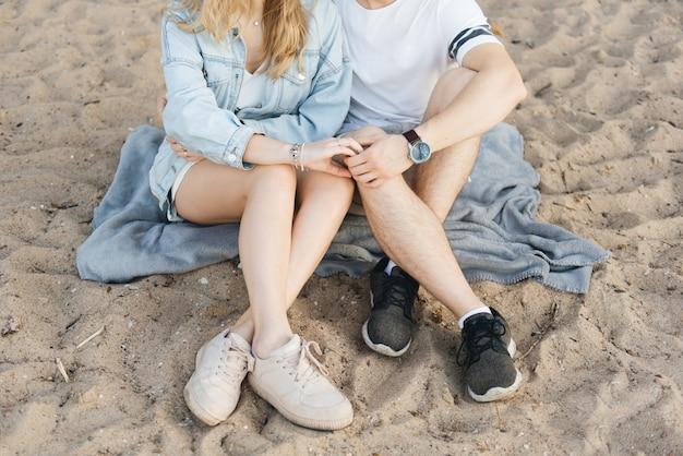 Verliefde paar hand in hand zittend op het zand close-up van handen