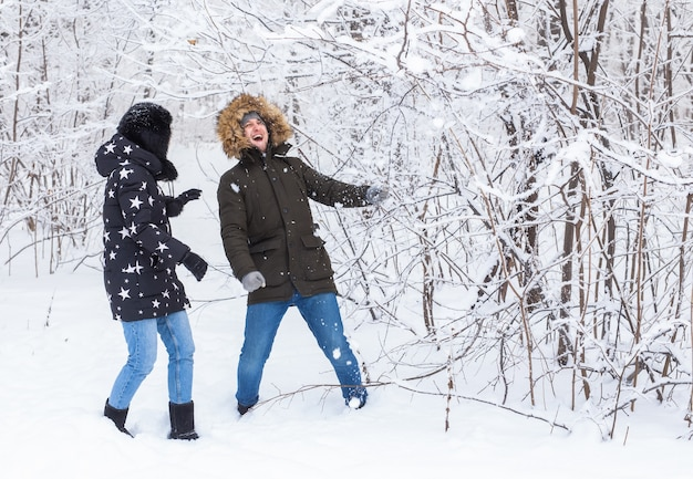 Verliefde paar hebben plezier in het besneeuwde bos. actieve wintervakantie.