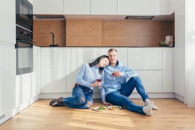 Verliefde paar het eten van een salade van groenten, zittend op de vloer in de keuken en het drinken van wijn