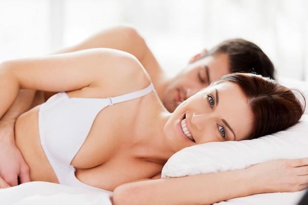 Verliefde paar in bed. mooie jonge verliefde paar liggend in bed terwijl vrouw camera kijken en glimlachen