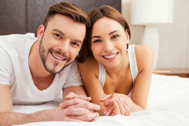Verliefde paar in bed. mooie jonge verliefde paar samen in bed liggen en glimlachen