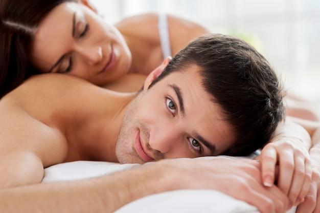 Verliefde paar in bed. vrolijke jonge verliefde paar in bed liggen en glimlachen naar de camera