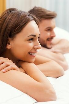 Verliefde paar in bed. zijaanzicht van mooie jonge verliefde paar samen in bed liggen en glimlachen