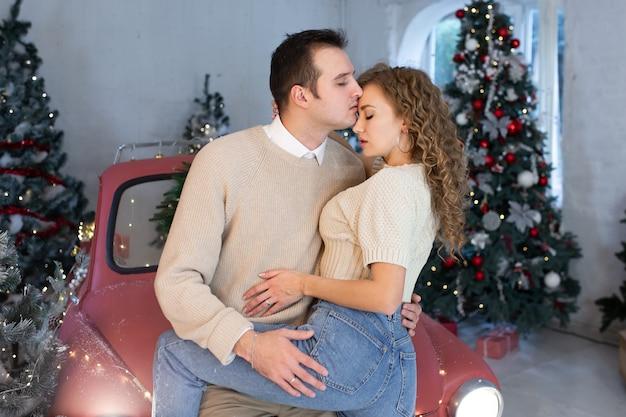 Verliefde paar in de buurt van mooi versierde kerstboom, genietend van de kerstmagie.