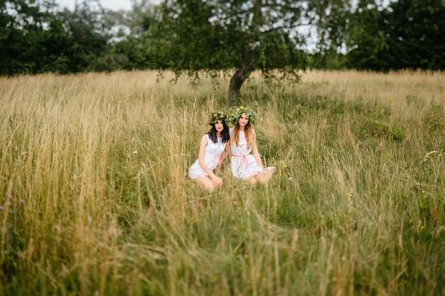 Verliefde paar in de natuur. twee heidense jonge meisjes van slavische vriendschap. vrouwen in traditionele russische kostuums. mooie meisjes met krans van bloemen samen in veld.