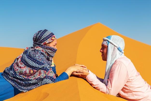 Verliefde paar in de saharawoestijn. gezamenlijke rust.
