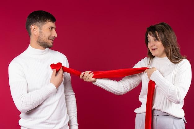 Verliefde paar in de studio op een rode achtergrond. dwaal rond en poseer met een liefdevol hart