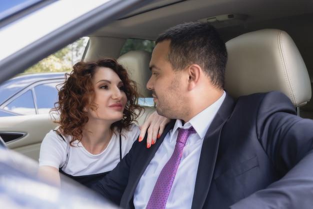Verliefde paar in een auto kijken elkaar teder aan