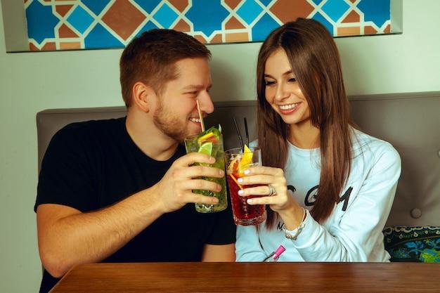 Verliefde paar in een café gerinkelcocktails met plezier en lachen