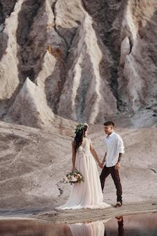 Verliefde paar in fantastische bergen knuffelen, martian landschap. liefhebbers wandelen in de bergen in de zomer, het meisje in lange lichte zomerjurk met een boeket bloemen en een krans op haar hoofd