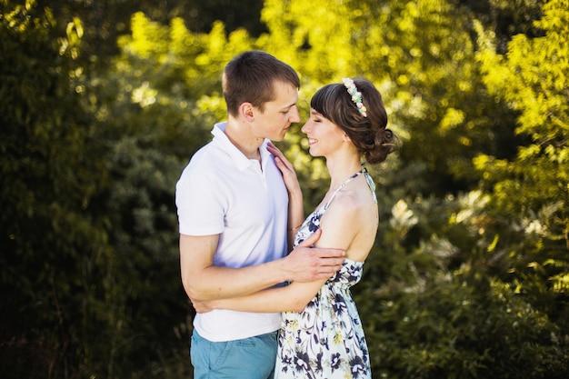 Verliefde paar in het berkenbos. man en vrouw lopen op de natuur. elkaar knuffelen. wees blij. actieve levensstijl. zomer bos. warm zonsonderganglicht.