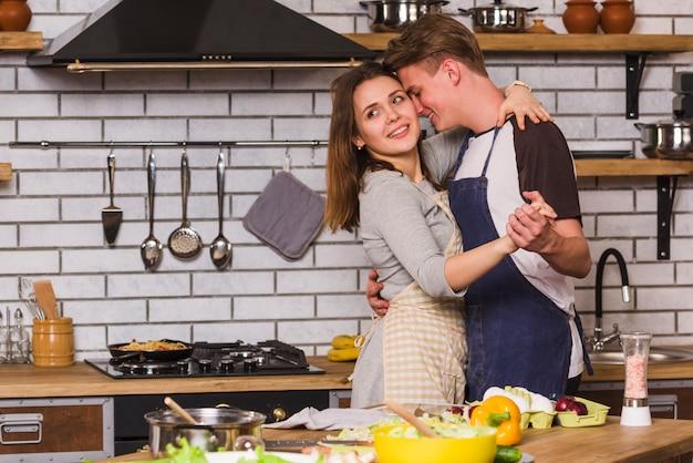 Verliefde paar in schorten dansen in de keuken