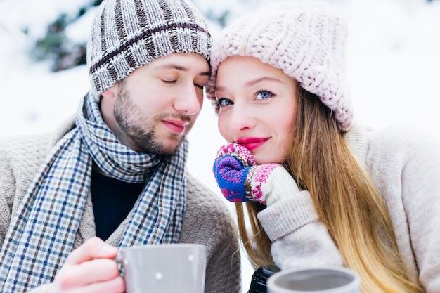Verliefde paar in warme kleren zitten een voor een in de sneeuw en houden de bekers in hun handen