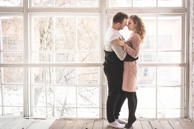 Verliefde paar in winterkleren bij het raam