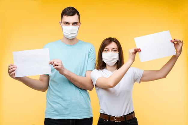 Verliefde paar in witte medische maskers zijn bang voor coronavirus en toont posters