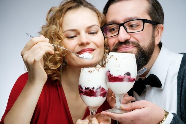 Verliefde paar kersenijs samen eten. man in de vlinderdas meisje in een rode jurk op een witte achtergrond
