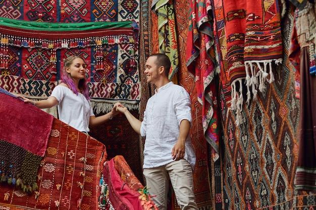 Verliefde paar kiest een turks tapijt op de markt. vrolijke vreugdevolle emoties op het gezicht van een man en een vrouw