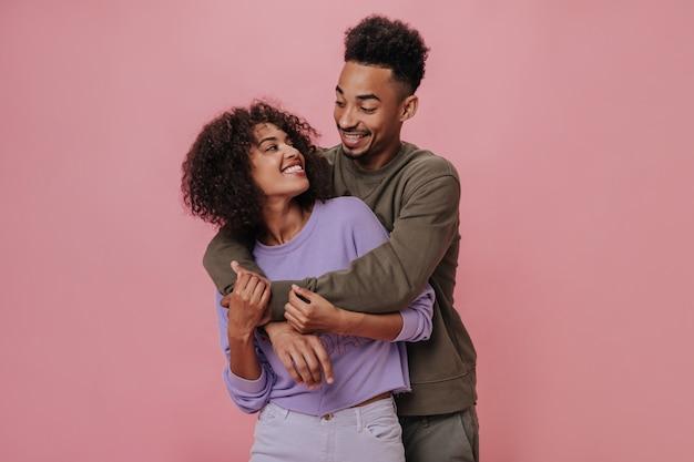 Verliefde paar kijken elkaar met liefde aan en glimlachen op roze muur