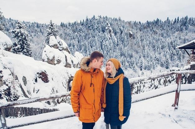 Verliefde paar knuffelen buiten in een sneeuwlandschap met zware winterjassen en bontmutsen.
